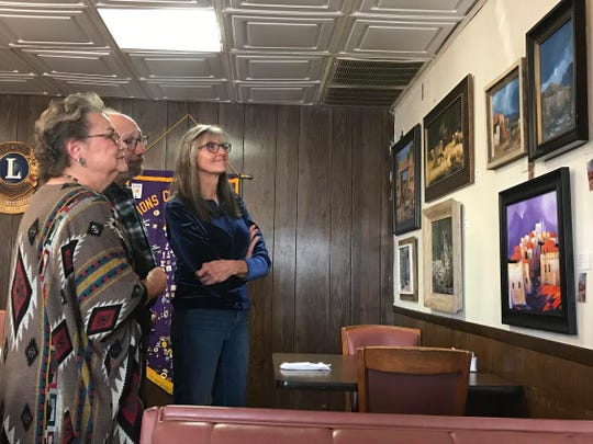At left, multi-medium artist Lyn Orona shows off five of her oil-based paintings to onlookers.