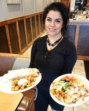 Abby Ammar holds two of Shawarma City's specialties: a chicken shawarma pita sandwich combo and the chicken shawarma meal with rice and herbed potatoes.