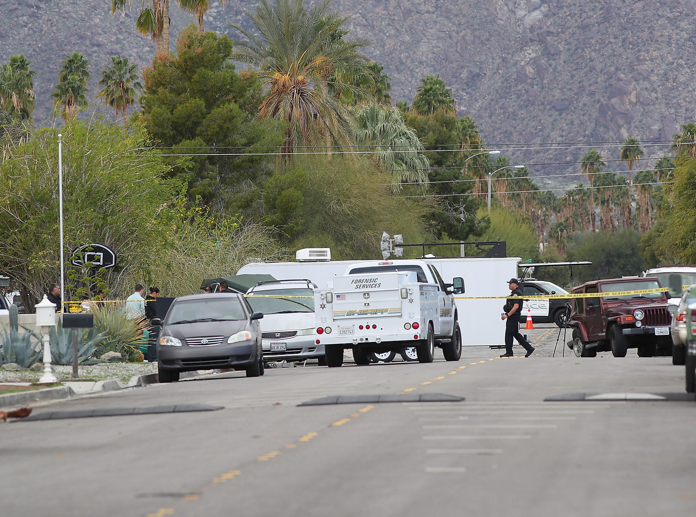 Police investigate the scene of an accident on Sunny Dunes Road in Palm Springs involving a car, hidden from view, on the left, February 4, 2019.