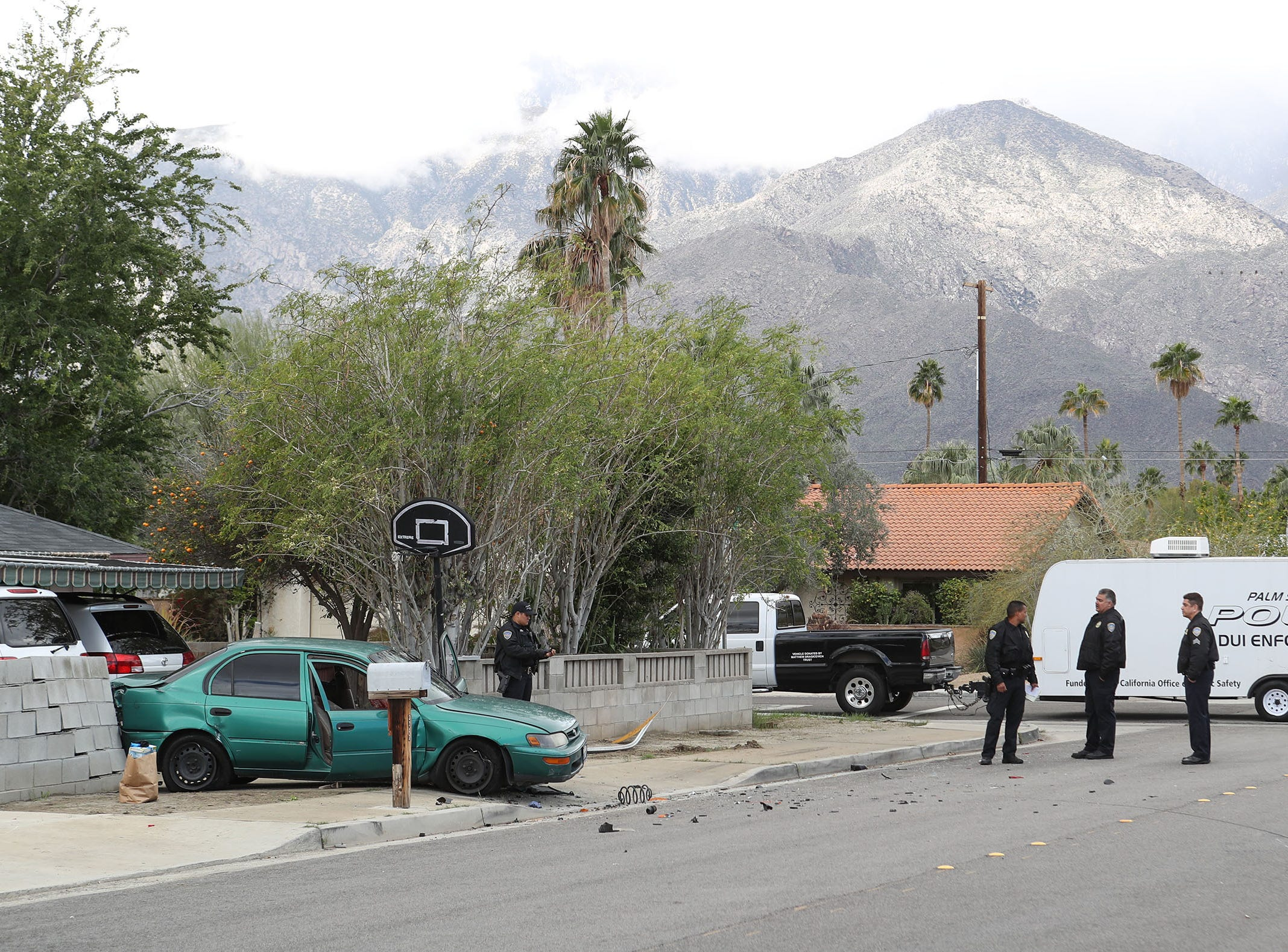 Police investigate the scene of an accident on Sunny Dunes Road in Palm Springs involving a green Toyota Corolla on February 4, 2019.