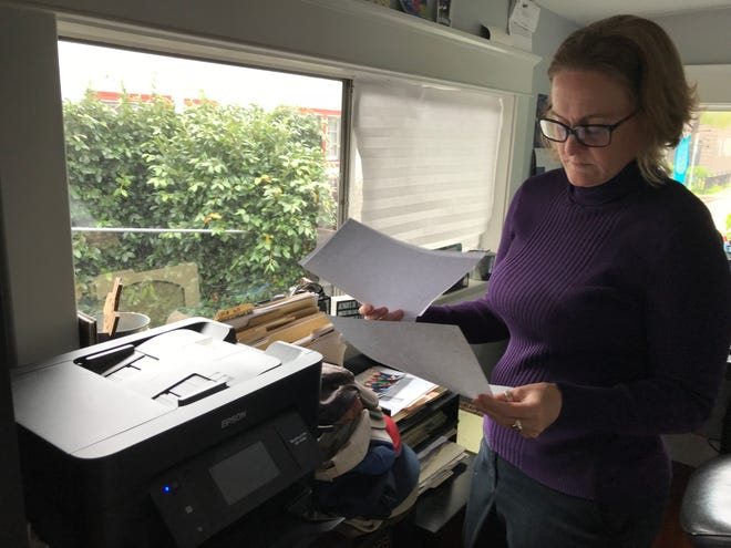 Heather Altman looks through old health insurance bills in her Long Beach home office.