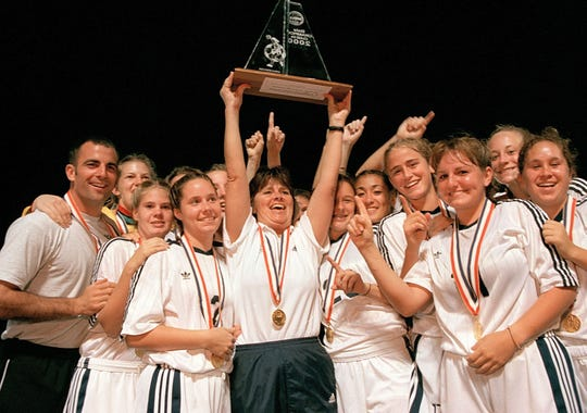 Gulf Breeze coach Pam Reynolds - surrounded by the team and coach Mike Lagow (left) holds high the state championship girls soccer trophy the Lady Dolphins won in Tampa on in 2000.
