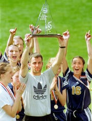 Gulf Breeze coach Mike Lagow holds the State Championship trophy high as his team celebrates beating Gulliver Prep 3-2 for the 2001 Class 2A Girl's State Championship.
