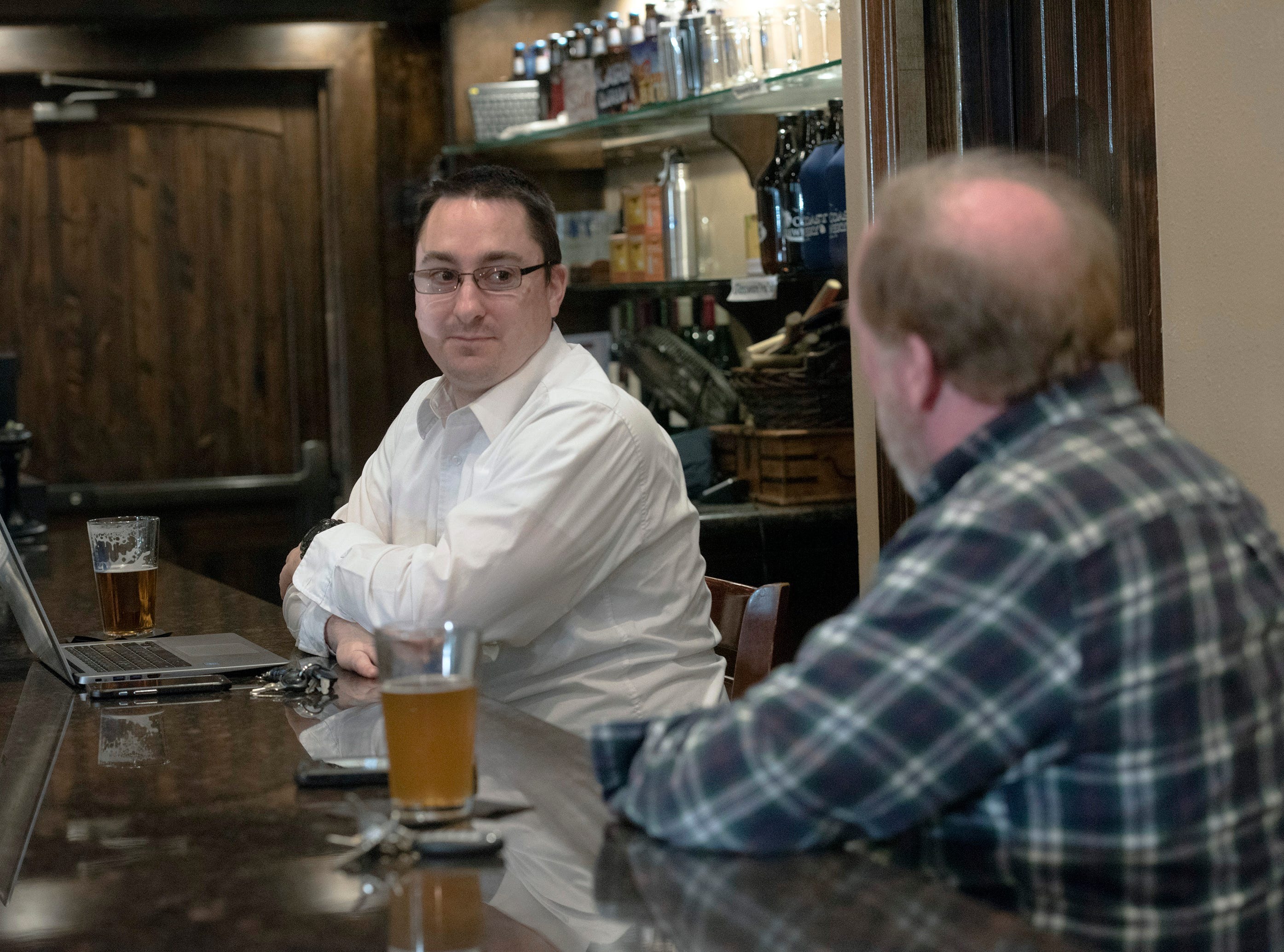 Mark Price and Tom Lehane, regular customers at the Gulf Coast Brewery, share a conversation and a beer on Thursday, Jan. 31. 2019. The craft brewery located on Heinberg Street in downtown Pensacola will soon celebrate its third anniversary.