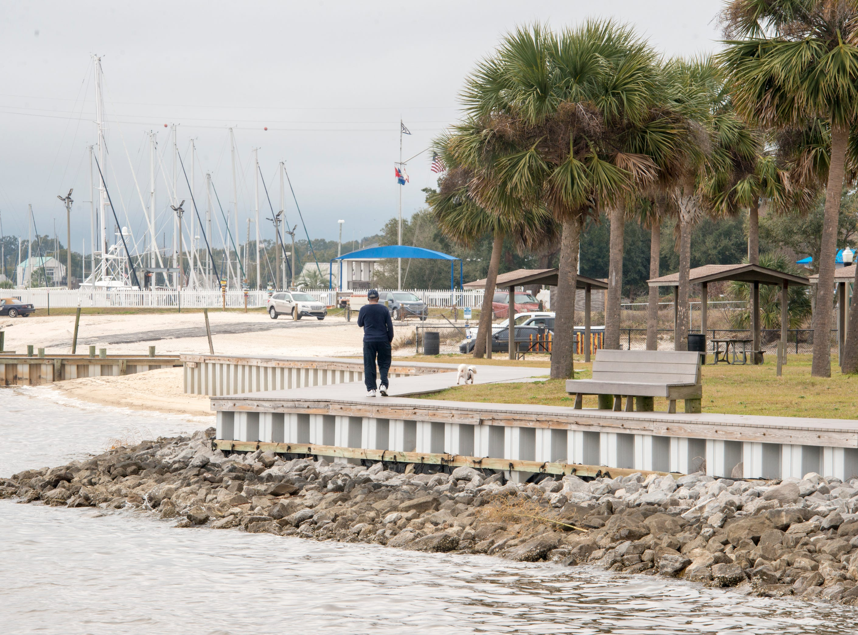 Joe Holmes walks his dog Bentley along the boardwalk at Sanders Beach in Pensacola on Monday, February 4, 2019.  Pensacola Mayor Grover Robinson plans to ask the Pensacola City Council for $60,000 to have the landscape architecture firm SCAPE study ways to improvement access, connectivity and resiliency along the waterfront between Joe Patti's Seafood to Bayou Chico. If approved, the funding would extend the boundaries of an existing SCAPE funded by Pensacola entrepreneur and philanthropist Quint Studer.