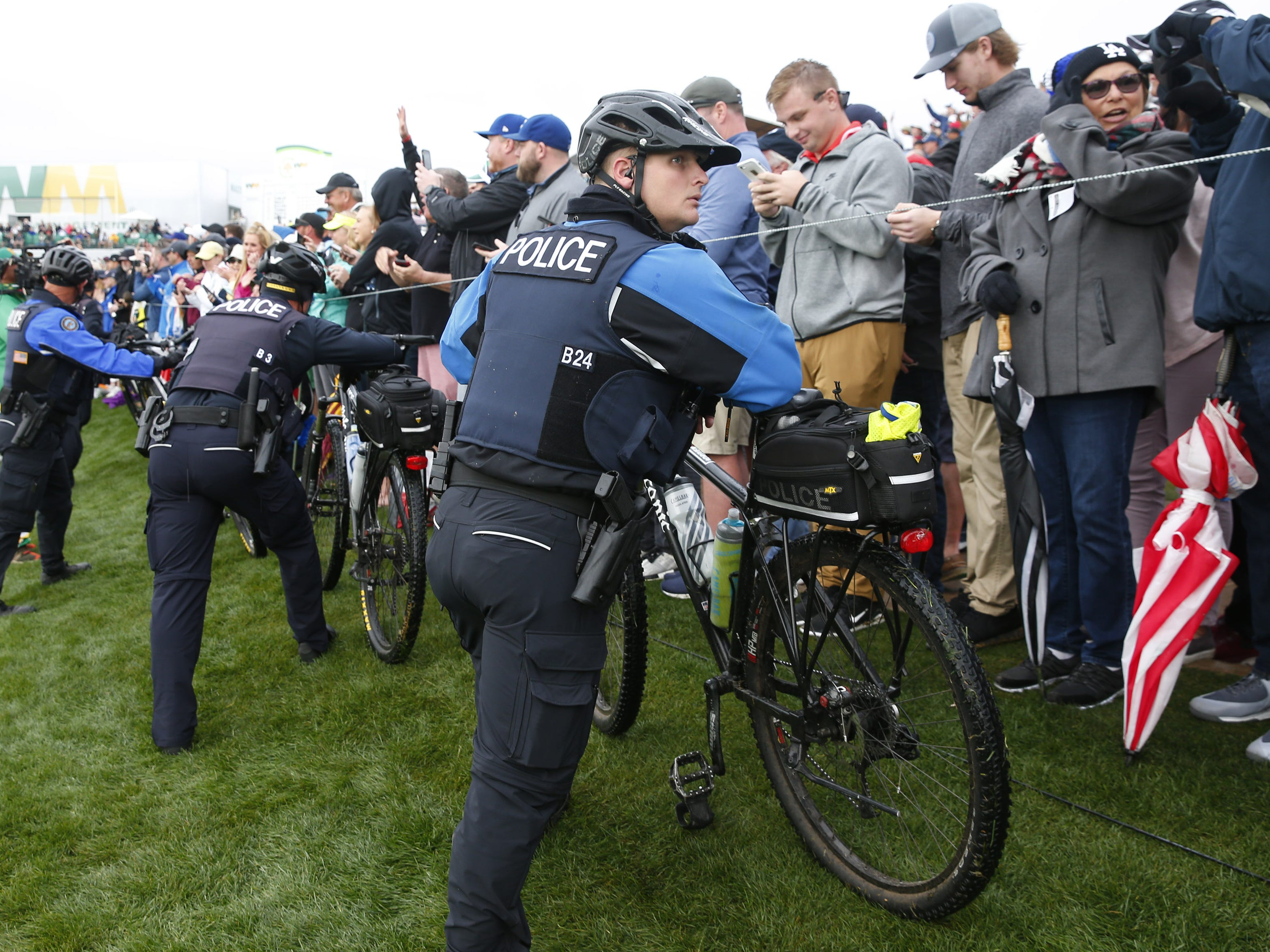Police use bikes to create a barrier between fans and the leaders on the 18th hole during the final round of the Waste Management Phoenix Open at the TPC Scottsdale Feb. 3, 2019.