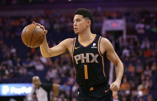 Devin Booker dribbles the ball during the first half of a game against the Hawks.
