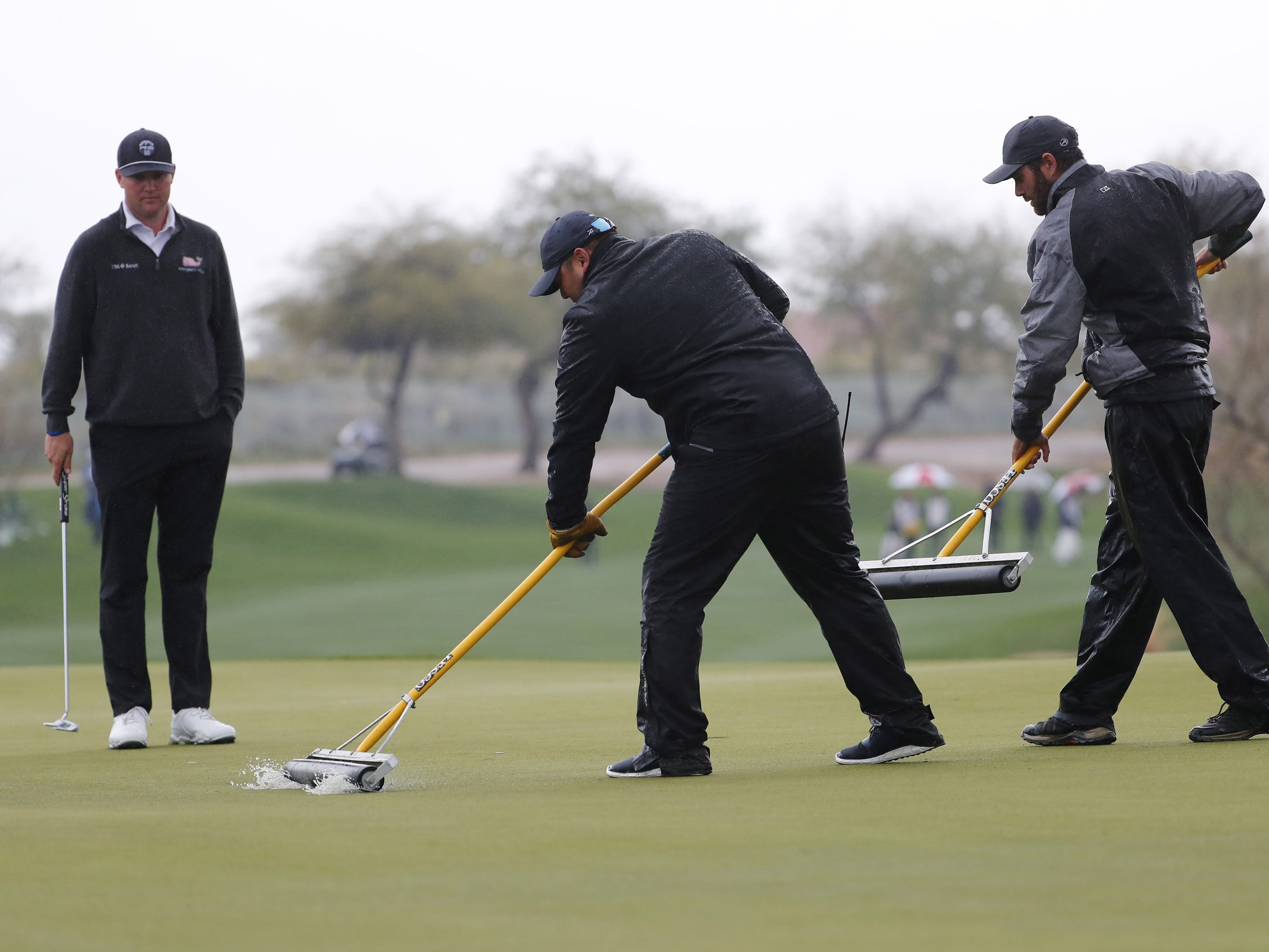 Grounds crew roll water off the 14th green during the final round of the Waste Management Phoenix Open at the TPC Scottsdale Feb. 3, 2019.