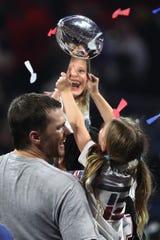 Tom Brady alza el trofeo con su hija en brazos.