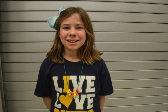 Fourth grader Kyleigh Nelson displays her necklace full of charms she earned in the Walking Club.