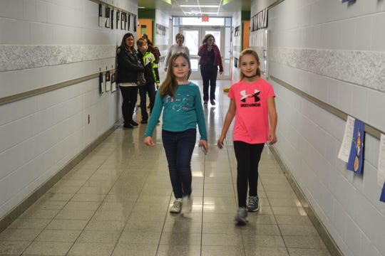 Fourth graders Macy Brandt, left, and Ella McCarthy walk the halls at Woodmore Elementary and Middle School as part of the Walking Club.