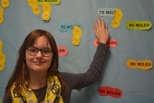 Seventh grader Katie Pittman points to her name tag on the bulletin board showing she has walked over 75 miles in the Walking Club. Pittman is the school's top walker.