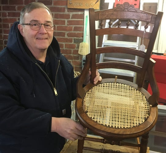 "Steve Ambrose shows a chair seat in the process of being cane woven. While working, he often listens to country music on an ""AM-FM 8-transistor analog radio"" in the garage behind his home."