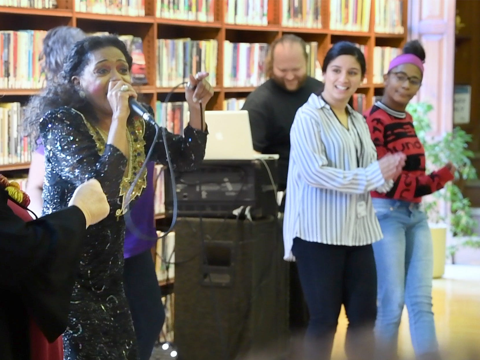 Vanda Guzman pulls people to the stage during a free concert at Martin Library on Sunday.