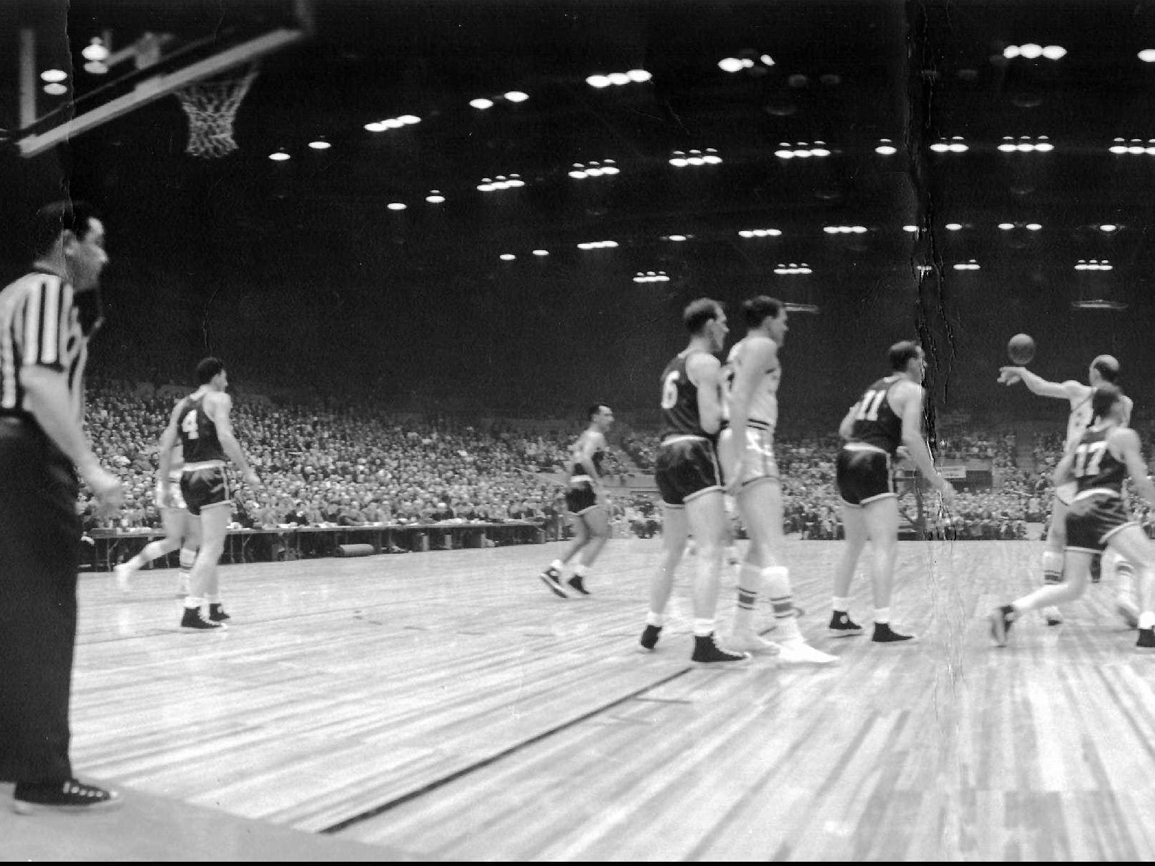 A scene from the 1956 NBA All-Star game at the Rochester War Memorial.  #4 is Dolph Schayes, heading down the court in the center of the photo is Bob Cousey.