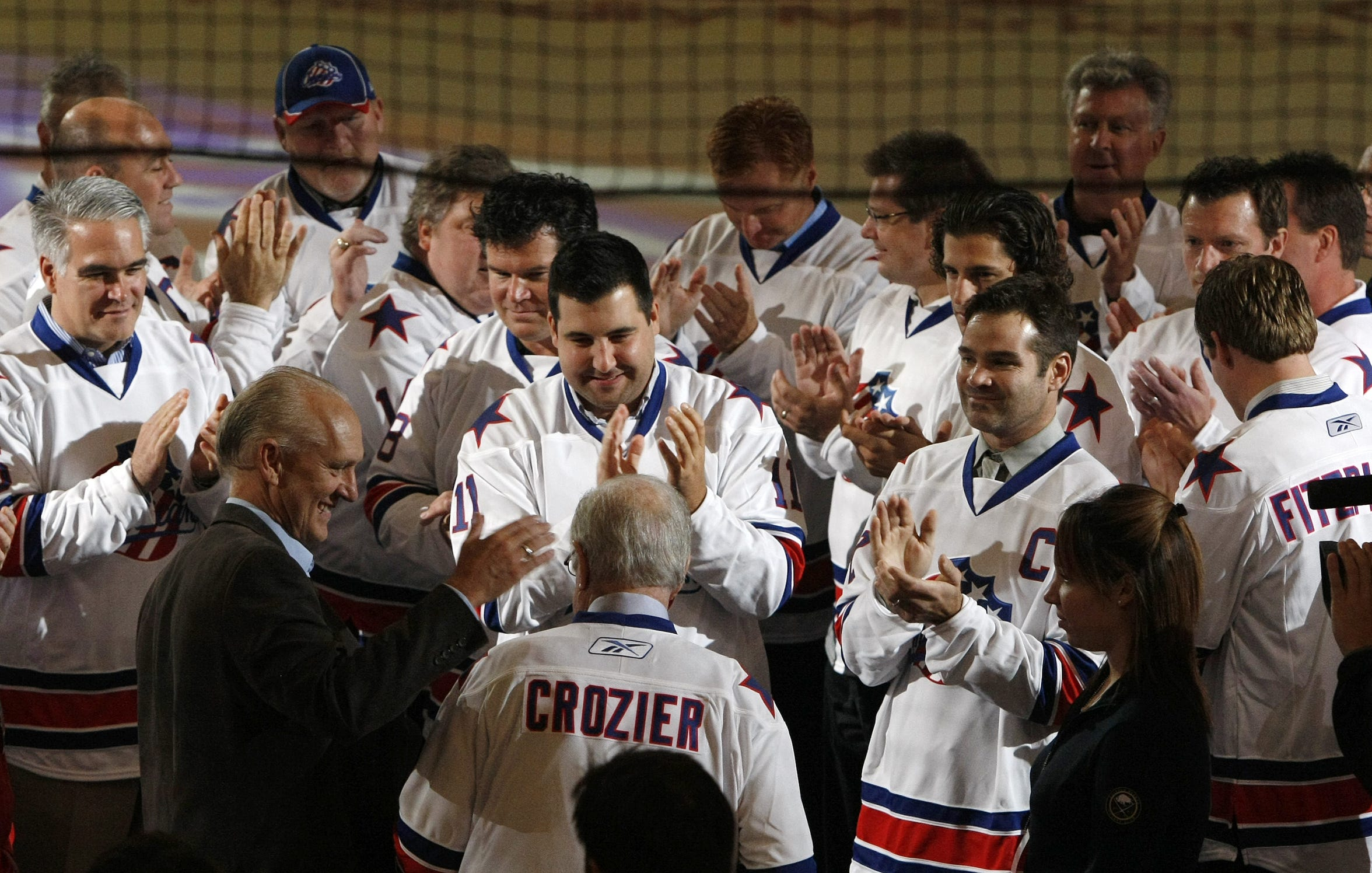 Five decades of Rochester Americans alumni show respects to former coach Joe Crozier, bottom center, as he was announced as the next inductee into the  American Hockey League Hall of Fame, during pregame ceremonies prior to the Amerks home opener between the Wilkes-Barre/Scranton Penguins on Oct. 13, 2011.