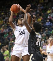 Oregon's Ruthy Hebard, left, shoots over Colorado's Mya Hollingshed during the first half of an NCAA college basketball game Sunday, Feb. 3, 2019, in Eugene, Ore.