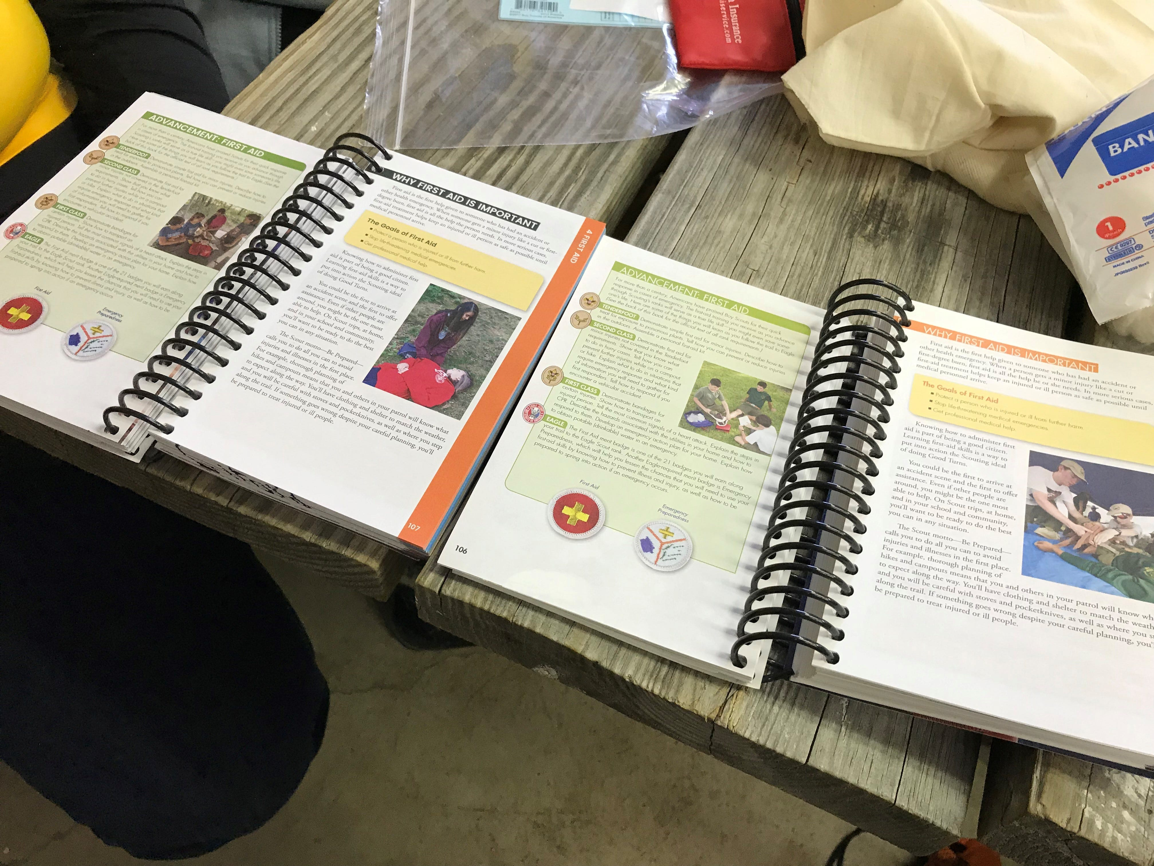 The scouting handbooks side by side. The book on the left is the revamped Scouts BSA handbook that features young women learning the same skills as the young men in the former Boy Scouts branch of the Boy Scouts of America. The book on the right is the older handbook which only featured young men.