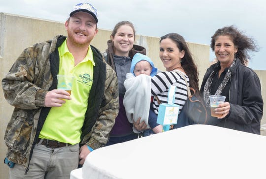 Gabriel Atkinson, left, with Islamorada Beer Co., Amber Small, Lauren, Levi and Patti Shrum on the roof of the Fort Pierce City Parking Garage for Bluebird Educational Foundation's Groovin' & Tastin' Sunrise City Wine & Spirits Fest.