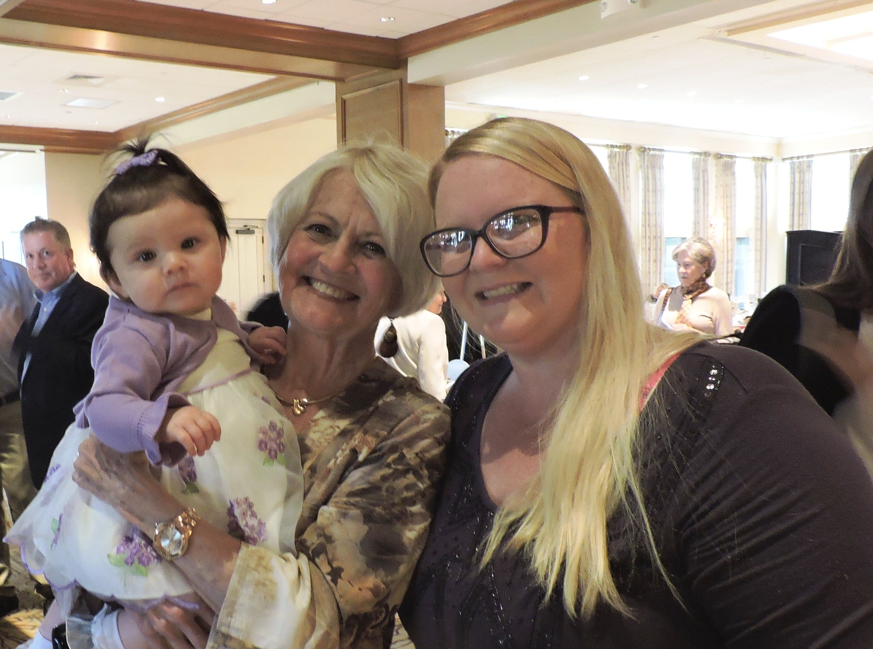 Diane Robinson, left, holds Madison as she talks with Mary's Shelter graduate and mom Jessica Bright at Mary's Shelter's Fashion Show & Luncheon Jan.22 at Willoughby Golf Club in Stuart.
