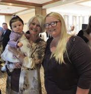 Diane Robinson, left, holds Madison as she talks with Mary's Shelter graduate and mom Jessica Bright at Mary's Shelter's Fashion Show & Luncheon Jan. 22 at Willoughby Golf Club in Stuart.