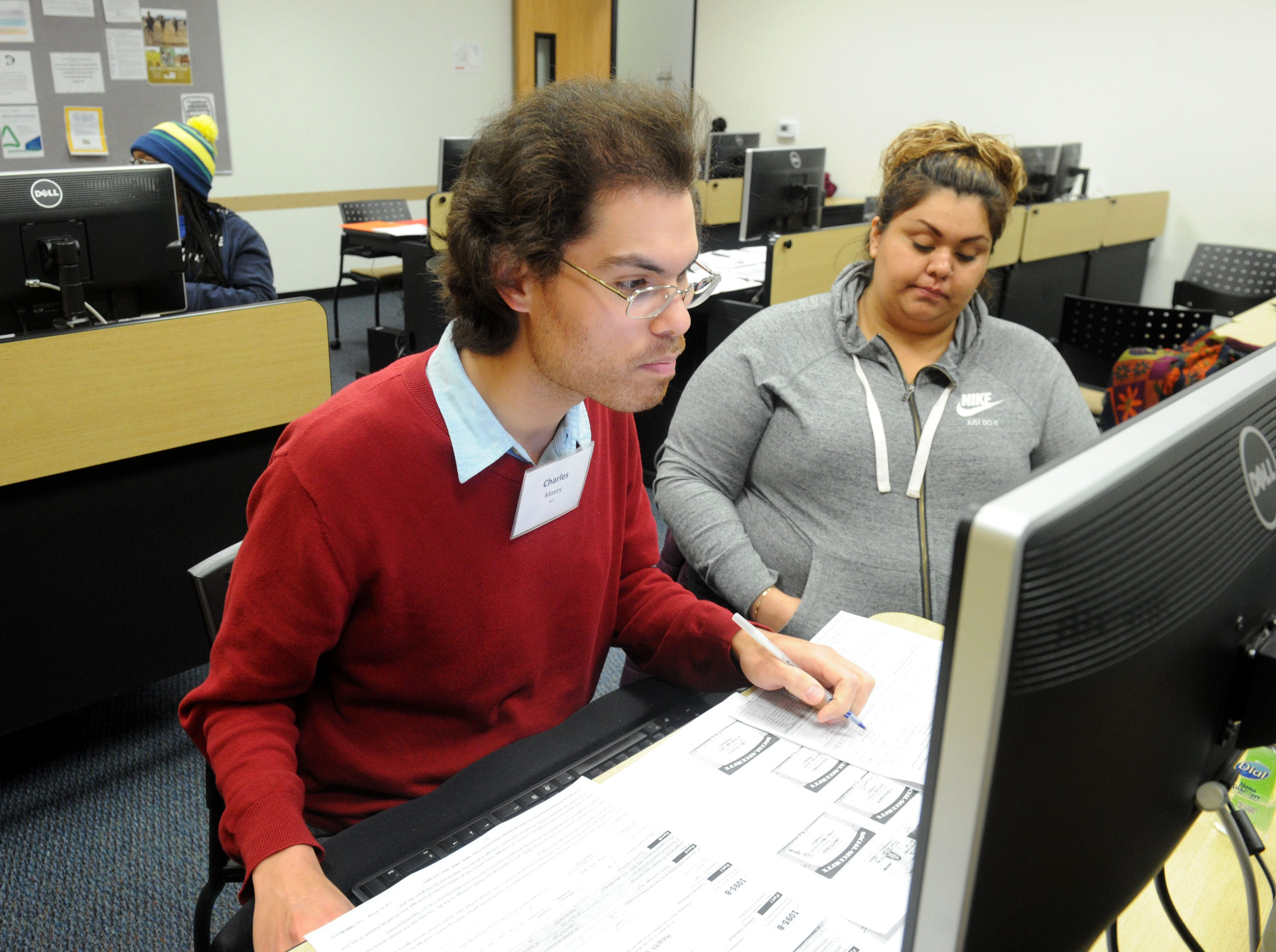 Charles Maxey, left, helps Sabrina Virgen  with her taxes recently through the United Way's Volunteer Income Tax Assistance program.
