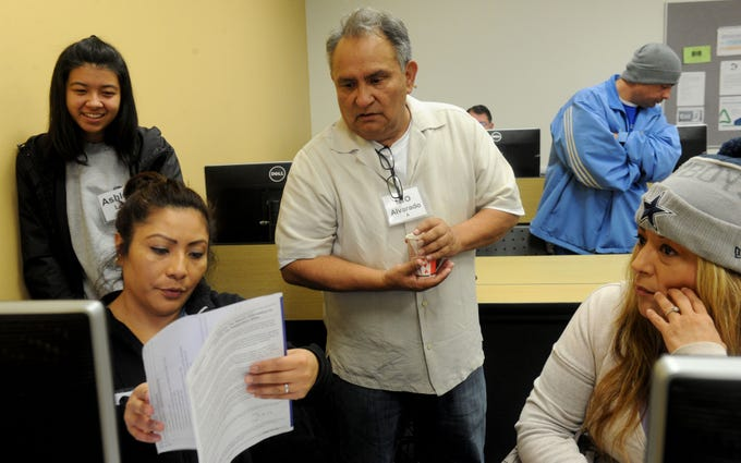 From left, volunteers Ashley Lee, Aimee Sosa and Lio Alvarado with the United Way of Ventura County help Yvette Estrella with her taxes at the California Lutheran University extension in Oxnard. The volunteers offer tax help as a free service to the community.