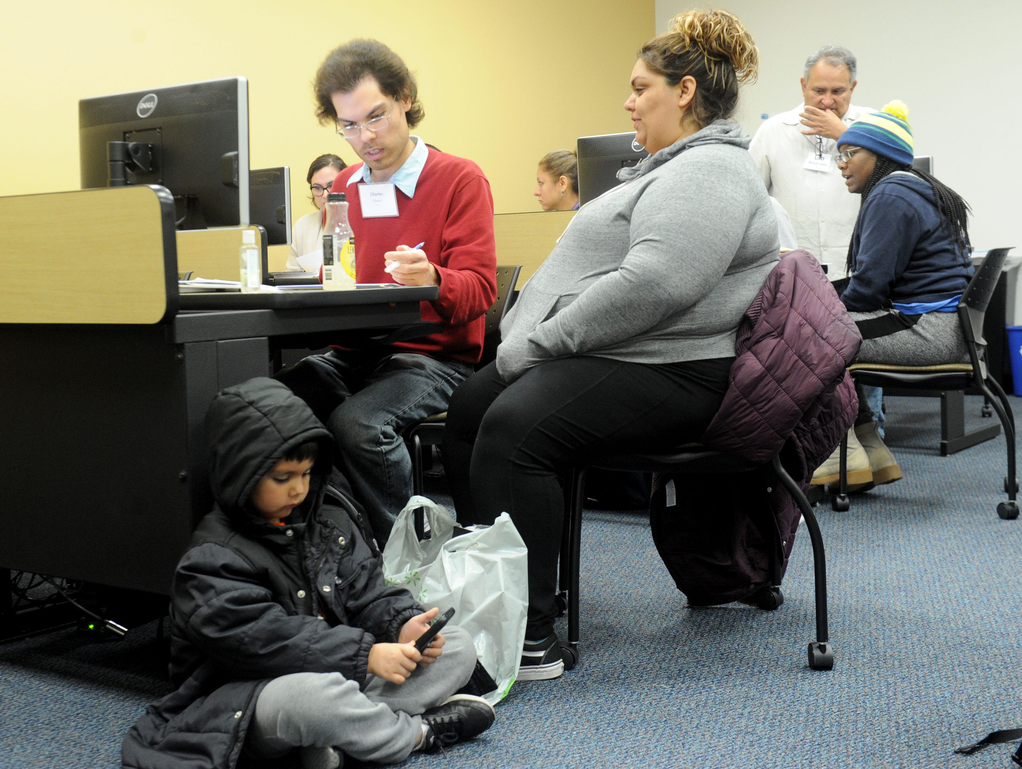 Volunteer Charles Maxey, left, helps Sabrina Virgen with her taxes as her son Jayden Fernandez plays games at the California Lutheran University extension in Oxnard.  The United Way's Volunteer Income Tax Assistance program assists households that earned less than $55,000 last year.