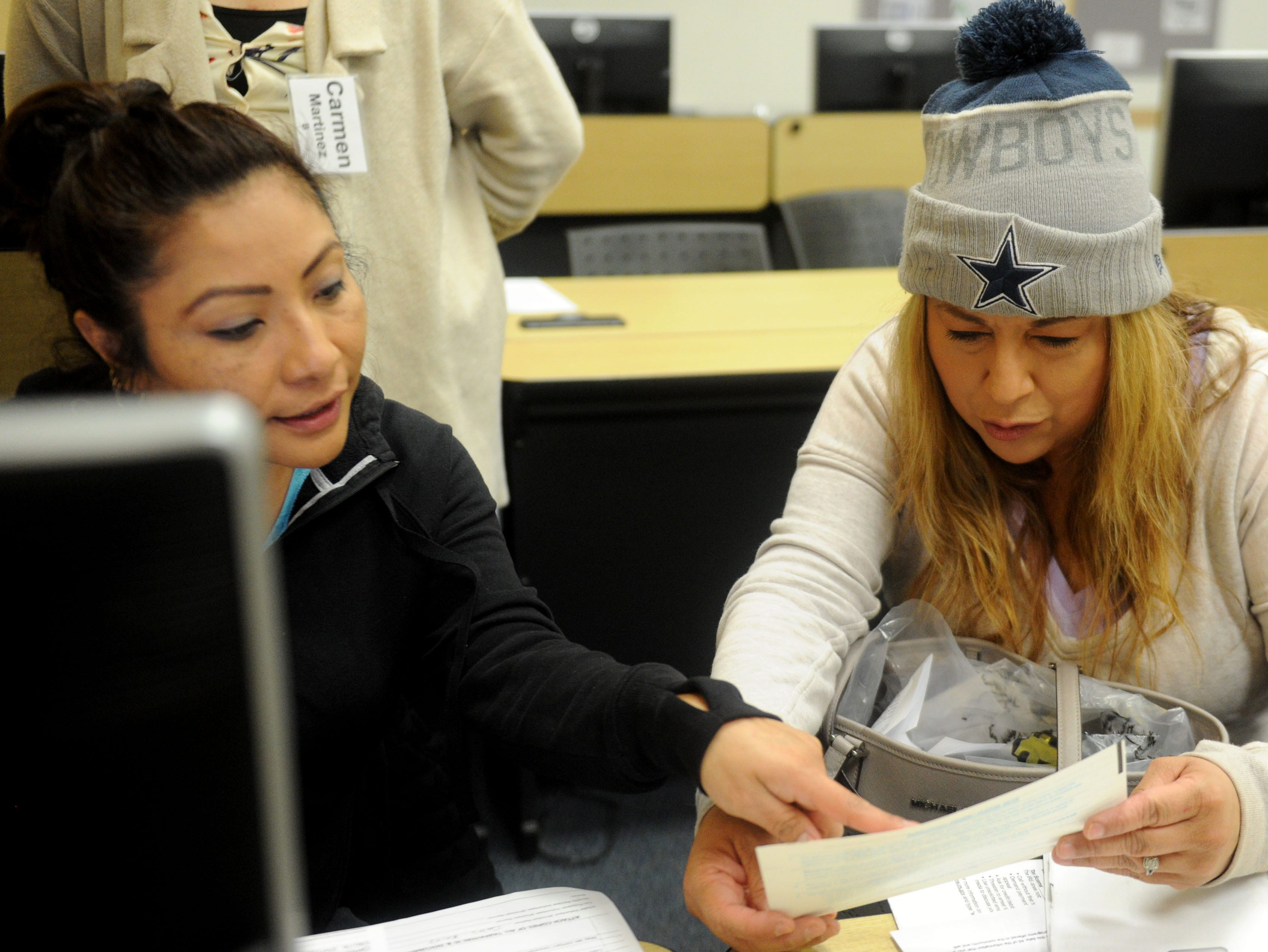 Aimee Sosa, left, helps Yvette Estrella with her taxes recently at the California Lutheran University extension in Oxnard as part of the United Way's free Volunteer Income Tax Assistance program.
