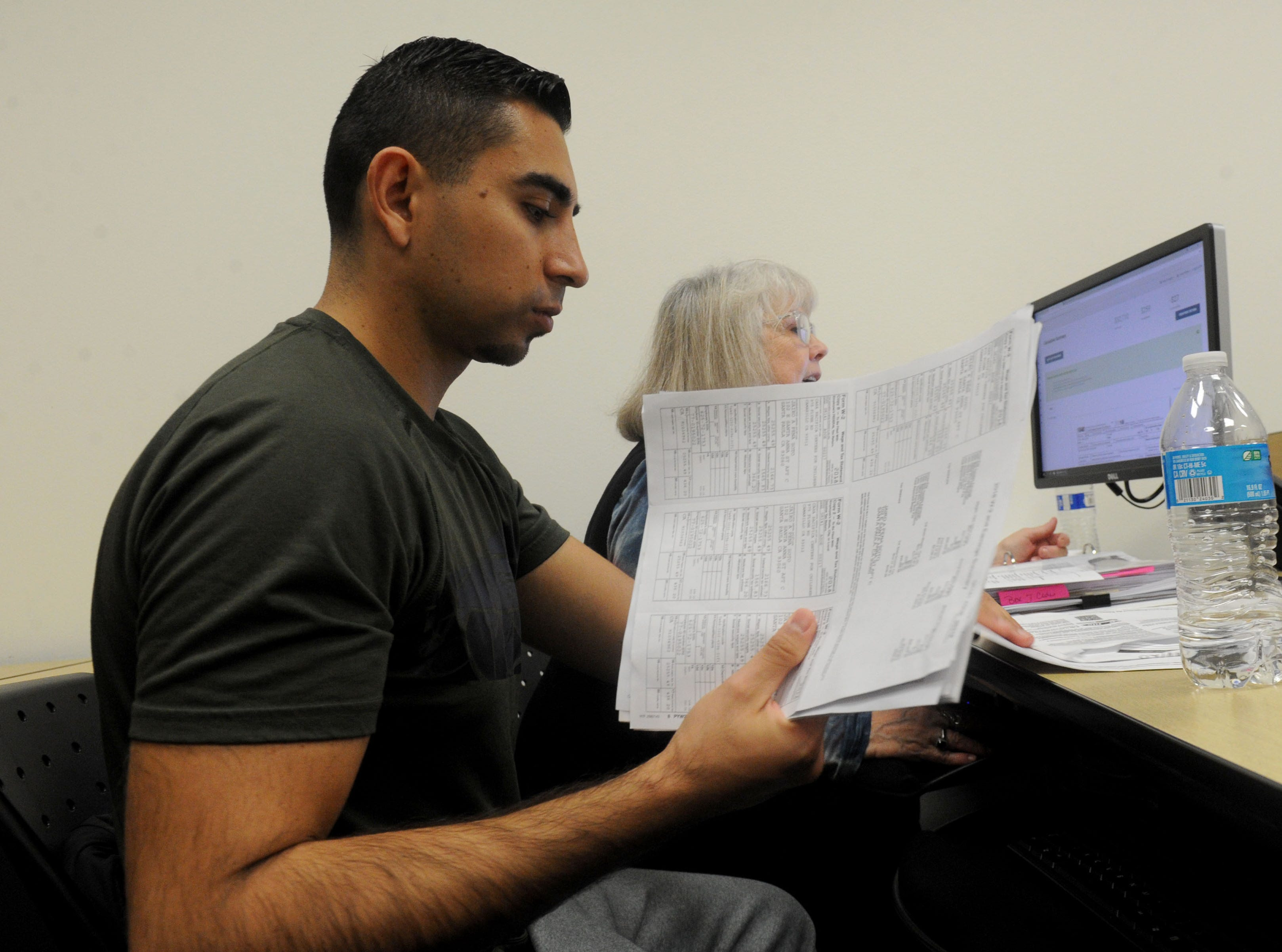 Jairo Pena, left, gets help with his taxes from Pam Grossman as part of the United Way's Volunteer Income Tax Assistance program. The organization's trained volunteers help households that earned less than $55,000