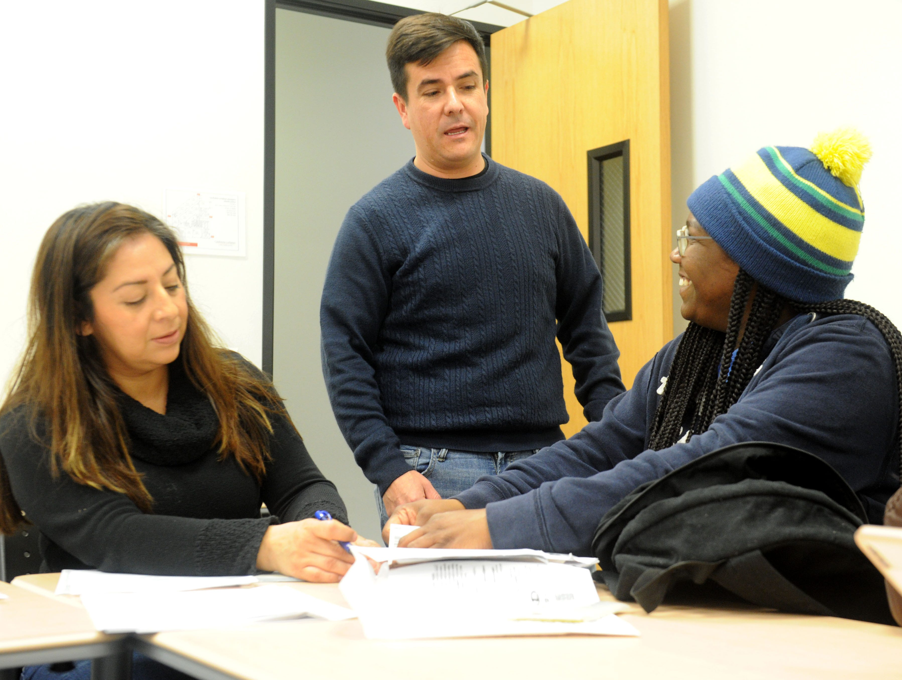 From left, Ayde Almaraz and Efrain De Santos help Frances Hart with her taxes  as part of the the United Way's Volunteer Income Tax Assistance program. The program is a free service to households that earned less than $55,000 last year.