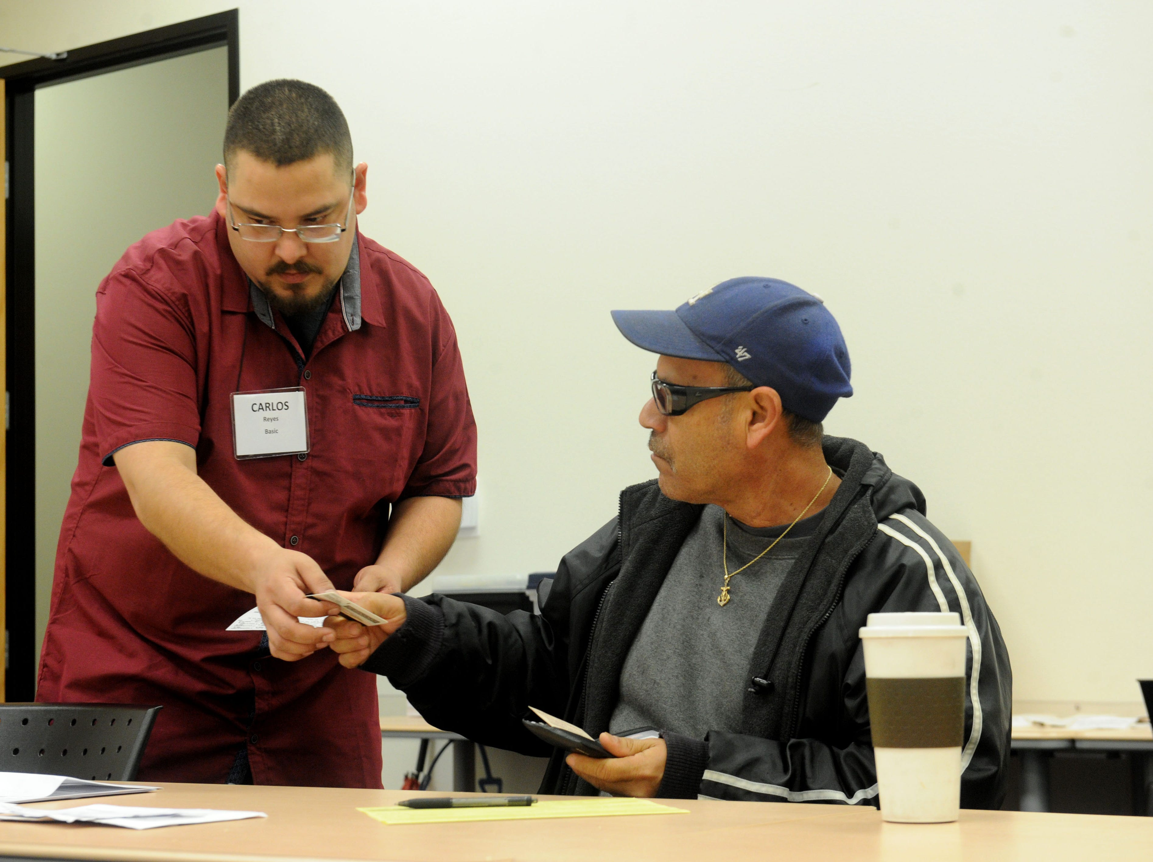 United Way volunteer Carlos Reyes, left, helps Luis Cruz get his tax paperwork organized recently at the California Lutheran University extension in Oxnard.