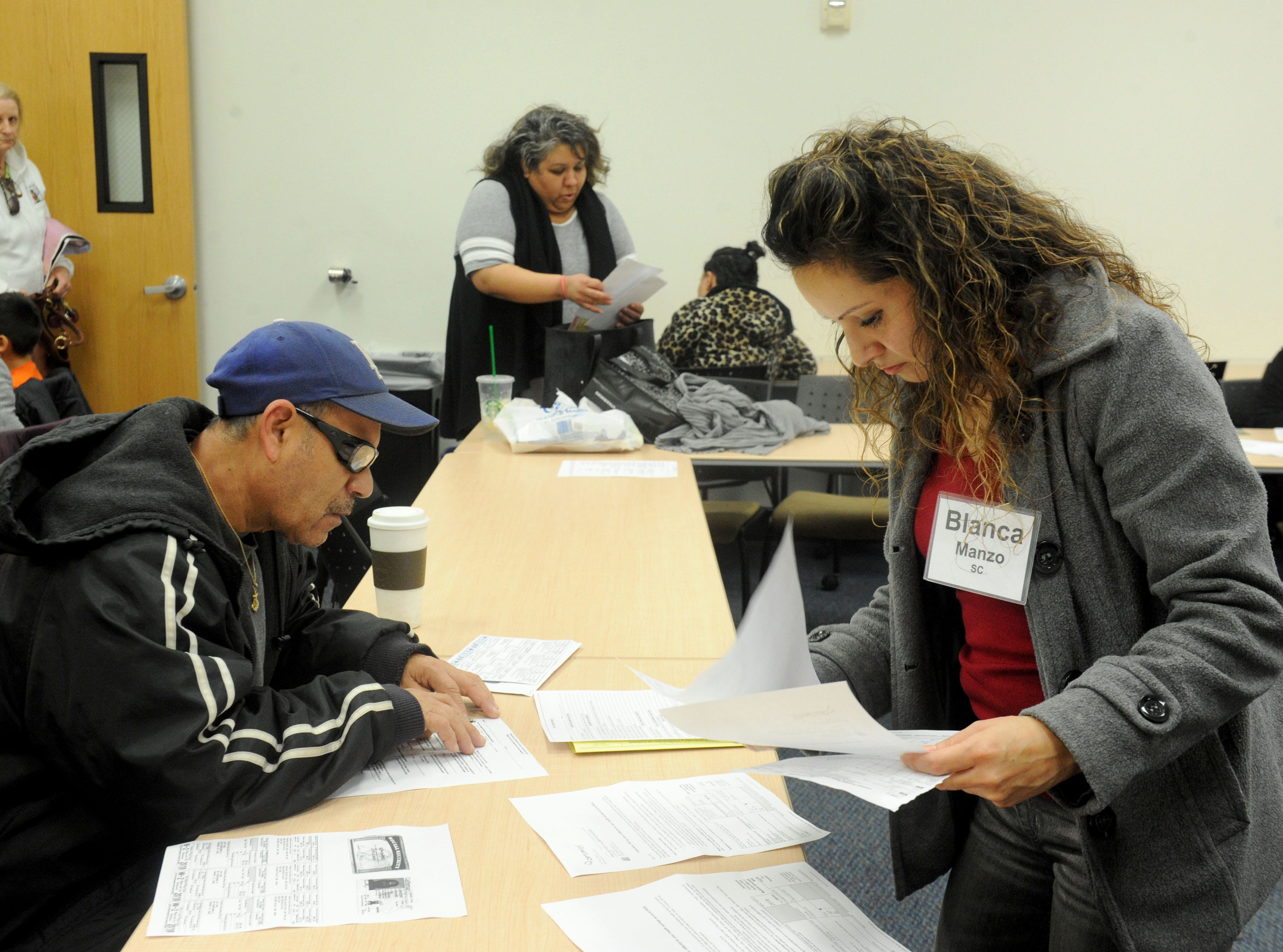 Luis Cruz, left, gets help on his taxes from Blanca Manzo through the United Way's Volunteer Income Tax Assistance program recently at the California Lutheran University extension in Oxnard.
