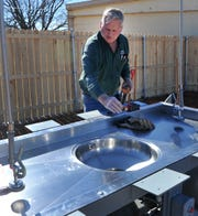 Brian's Plumbing journeyman plumber, Glen Kulhanek works to install a fish cleaning station at the Lake Wichita boat ramp located on Kemp Blvd. Monday morning.