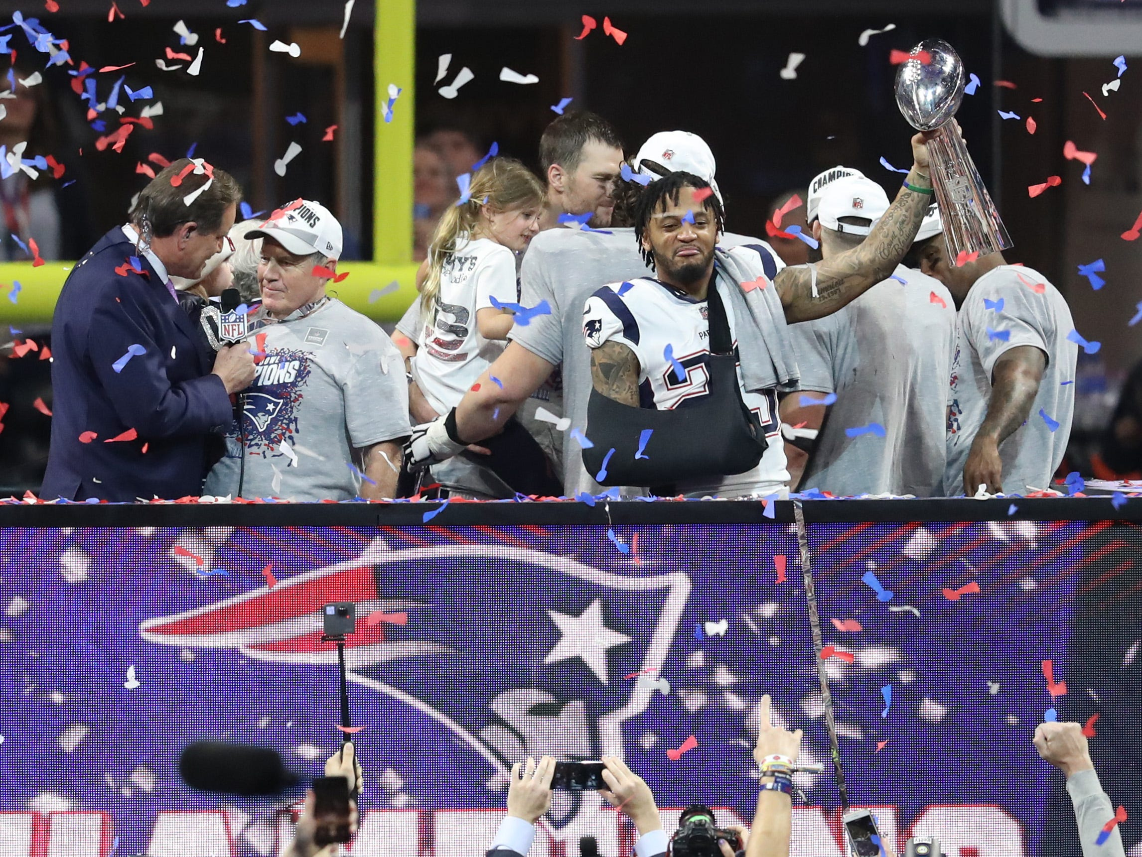 Safety Patrick Chung (23) lifts the Vince Lombardi trophy as head coach Bill Belichick talks with CBS host Jim Nance, left, after Patriots beat the Rams 13-3 in Super Bowl LIII.