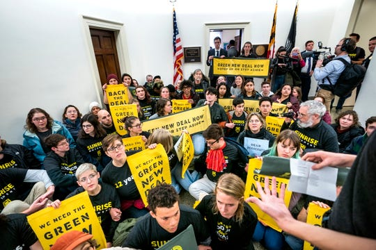"Supporters of then-Rep.-elect Alexandria Ocasio-Cortez's proposed select committee on a ""Green New Deal"" rally outside the office of Democratic congressman from Maryland and then-House Minority Whip Steny Hoyer in the Longworth House Office Building in Washington, D.C., December 10, 2018."