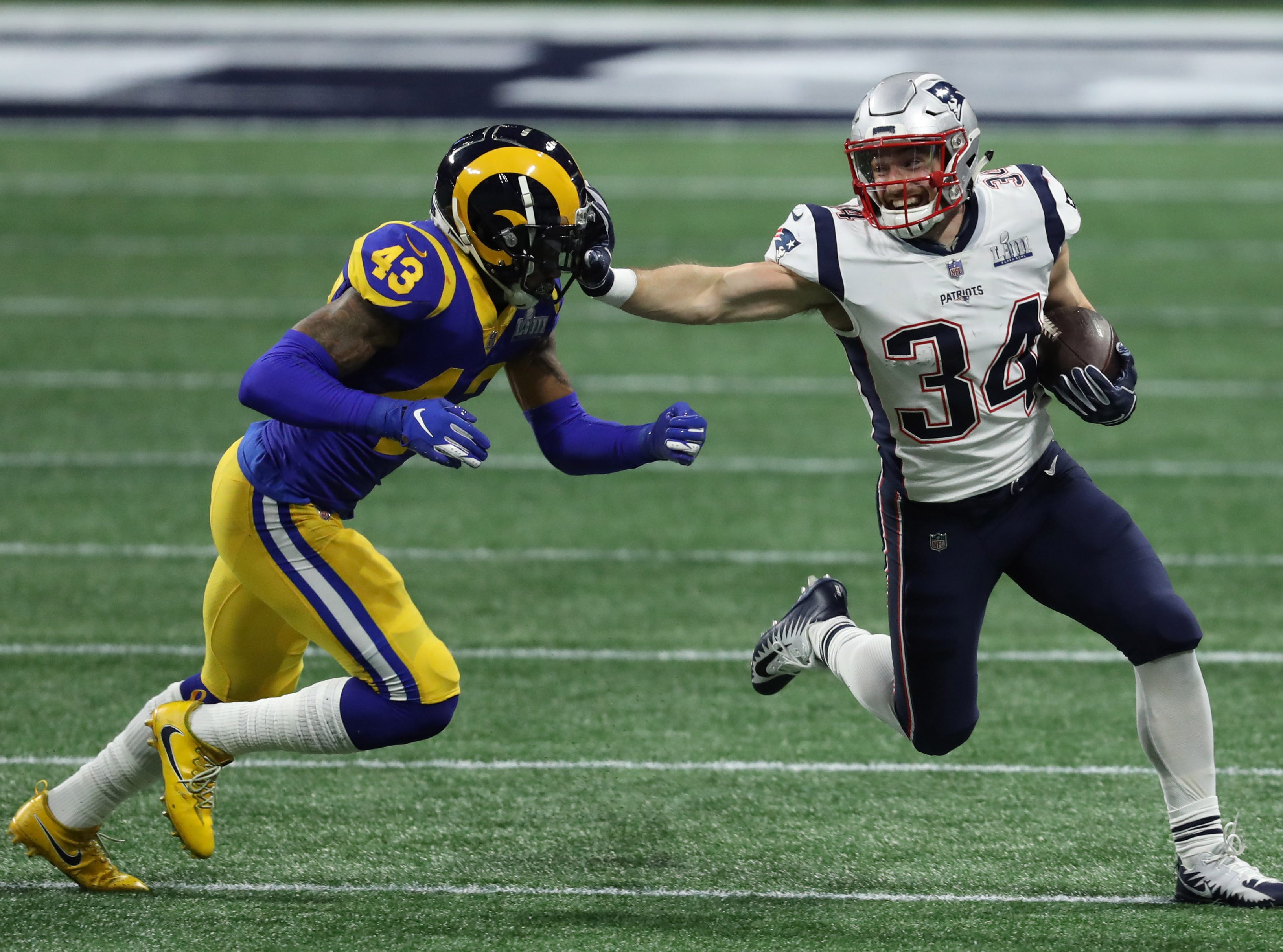 New England Patriots running back Rex Burkhead (34) breaks the tackled of Los Angeles Rams strong safety John Johnson (43) during the first quarter of Super Bowl LIII.