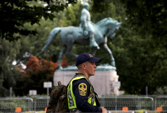 A member of the Virginia State Police waits outside the park where a statue of Confederate Gen. Robert E. Lee  is located August 11, 2018 in Charlottesville, Virginia.