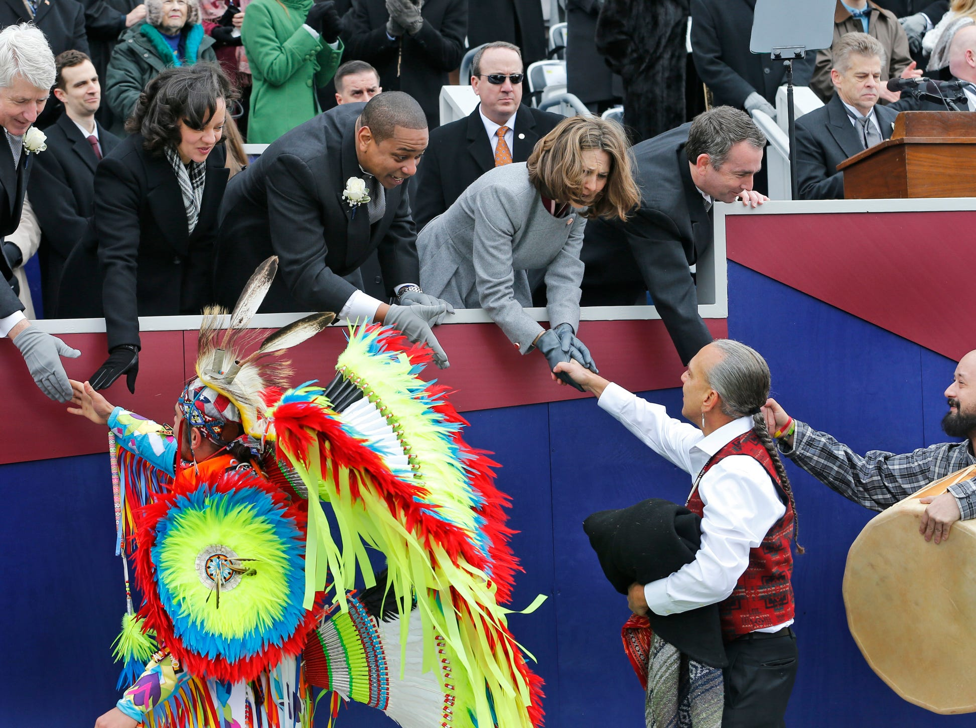 Members of the inaugural party, Attorney General Mark Herring, left, Cerina Fairfax, second from left, Lt. Gov. Justin Fairfax, center; first lady Pam Northam, second from right, and Gov. Ralph Northam greet Native American dancers during inaugural ceremonies at the Capitol in Richmond, Va., Saturday, Jan. 13, 2018. (AP Photo/Steve Helber)