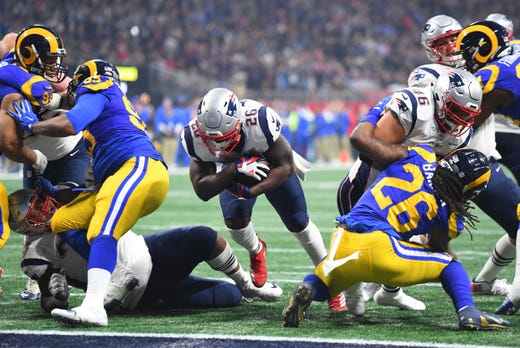 New England Patriots running back Sony Michel (26) cuts through a hole to score the game's first touchdown during the fourth quarter.