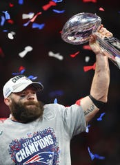Julian Edelman hoists the Vince Lombardi Trophy.