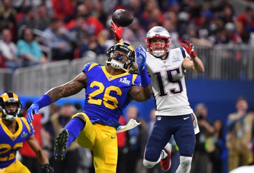 Los Angeles Rams inside linebacker Mark Barron (26) and New England Patriots wide receiver Chris Hogan (15) attempt to catch the ball during the first quarter of Super Bowl LIII.