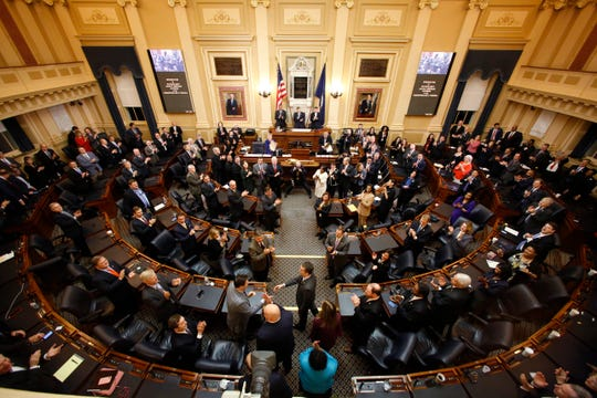 In this Wednesday, Jan. 9, 2019 file photo, Gov. Ralph Northam, center, arrives to deliver his State of the Commonwealth address during a joint session of the Virginia Legislature in the House chambers at the Capitol in Richmond, Va.