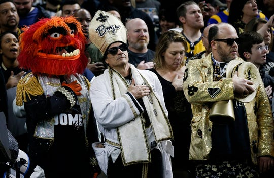 New Orleans Saints fans stand for the national anthem before the NFC Championship game against the Los Angeles Rams.