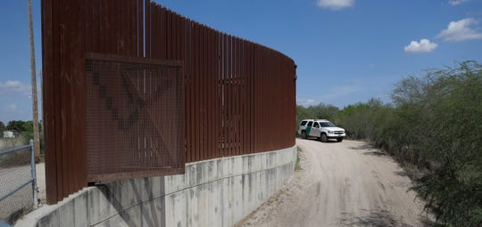 A Customs and Border Patrol vehicle passes along a section of border levee wall in Hidalgo, Texas.