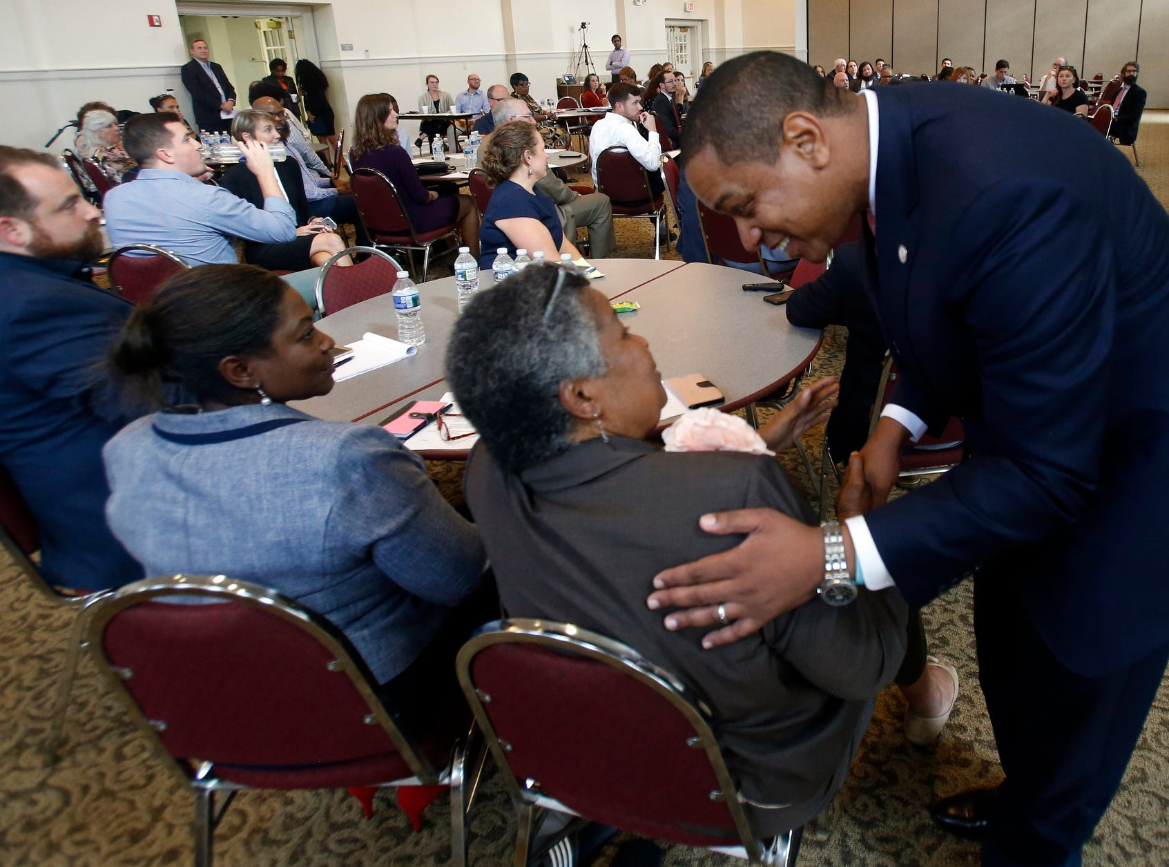 Justin Fairfax greets attendees after remarks at a meeting of the Campaign to reduce evictions at a church meeting room in Richmond, Va., on ,Sept. 25, 2018.
