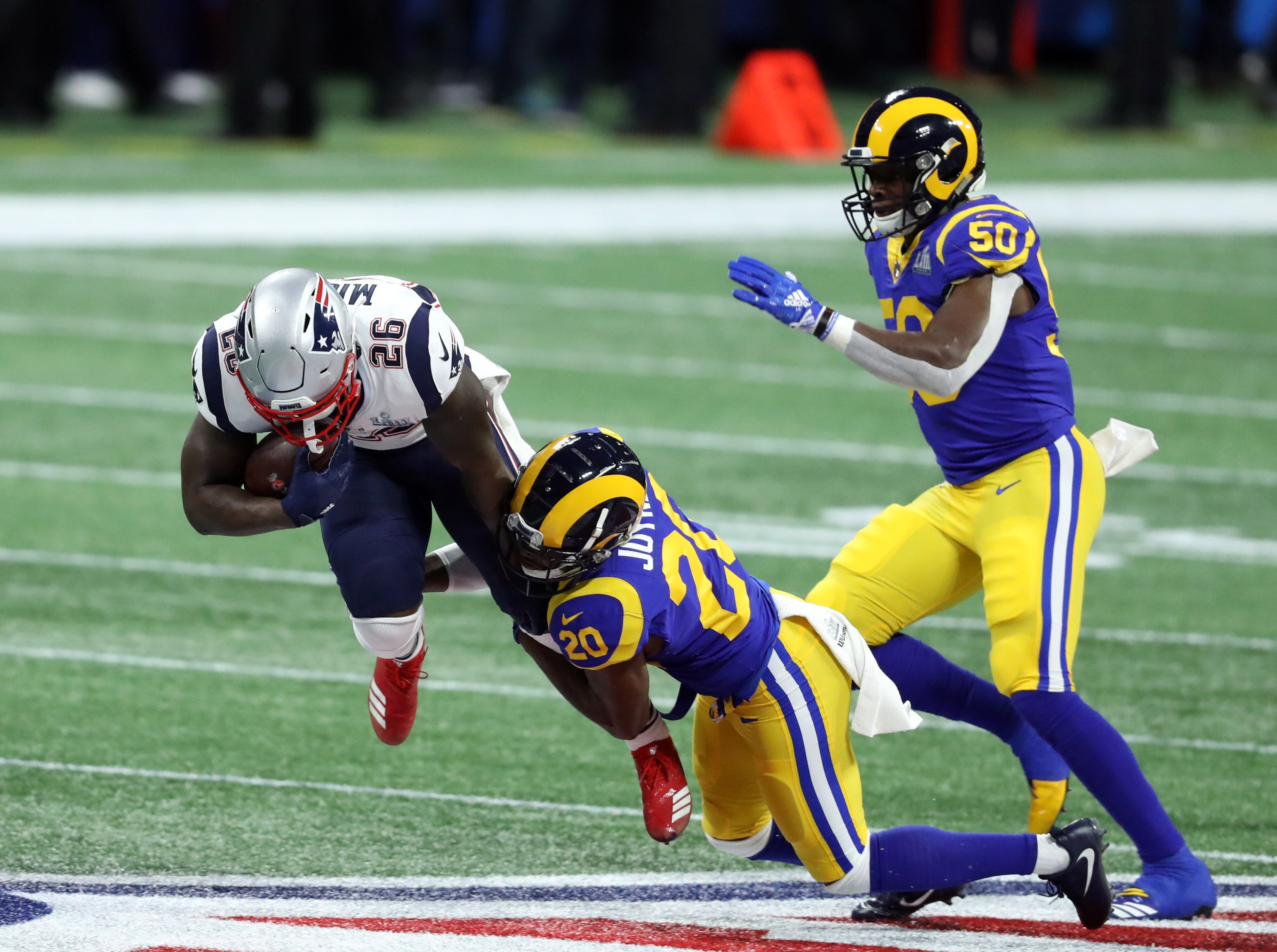 Los Angeles Rams free safety Lamarcus Joyner tackles New England Patriots running back Sony Michel (26) during the first quarter of Super Bowl LIII.