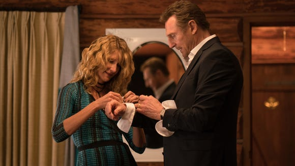 "Grace (Laura Dern, left) gets husband Nels (Liam Neeson) ready for a ""Citizen of the Year"" ceremony in ""Cold Pursuit."""