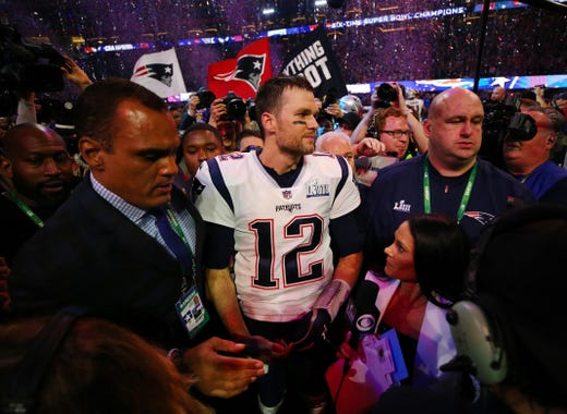 New England Patriots quarterback Tom Brady (12) gets mobbed by reporters on the field after defeating the Los Angeles Rams 13-3 in Super Bowl LIII and setting a record for most Super Bowl wins.