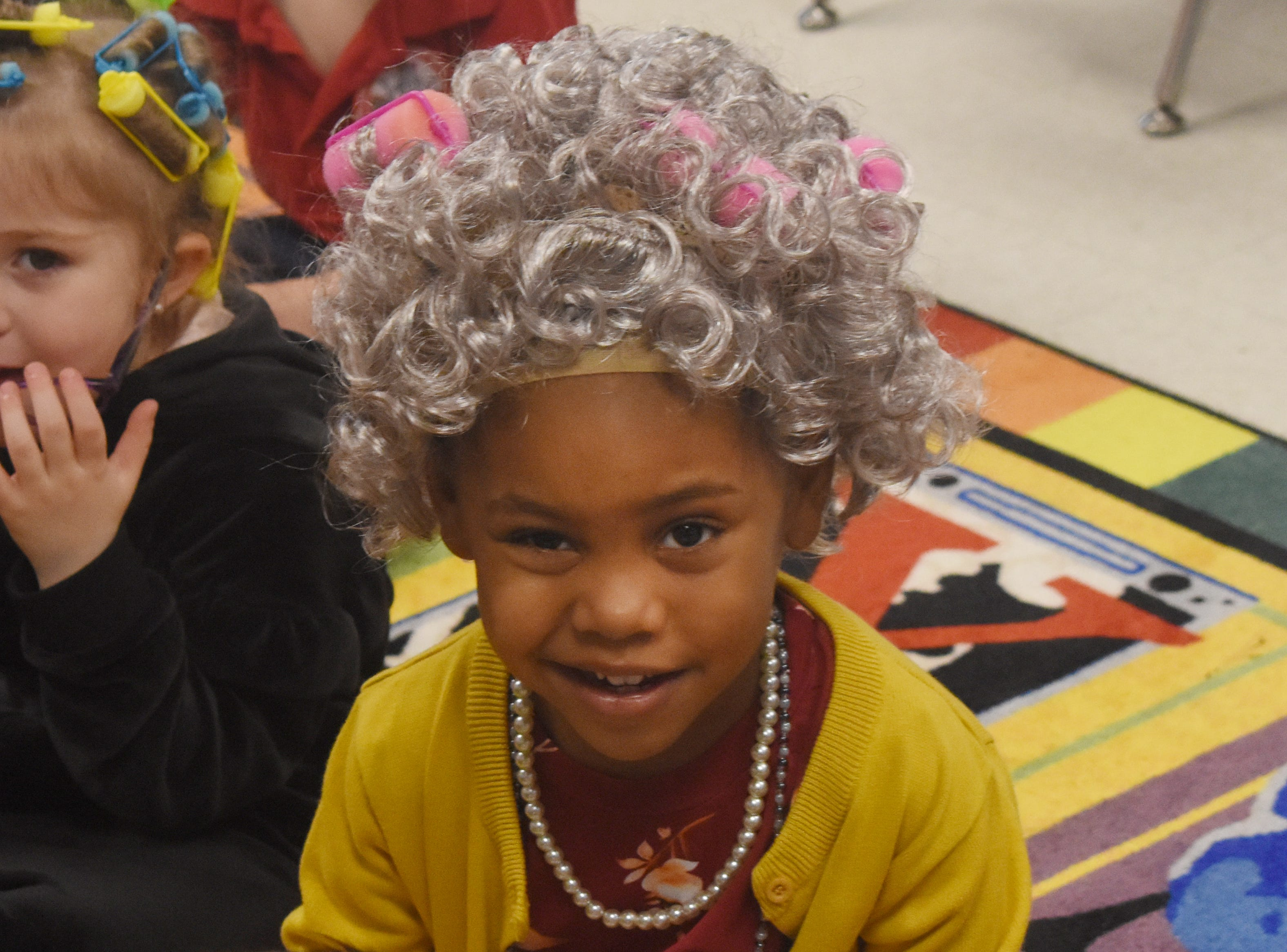 St. Frances Cabrini pre-Kindergarten student Alle Harris smiles while dressed in a curly gray wig with rollers, a pearl necklace and a cardigan. On Tuesday, Feb. 5, 2019, St. Frances Cabrini School pre-Kindergarten and Kindergarten students dressed up as 100-year-olds in celebration of 100 days of school.